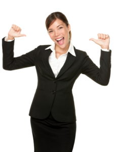 woman in suit pointing at self and smiling