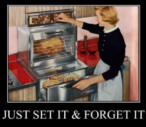 1950s housewife in front of rotisserie oven